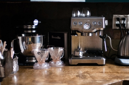 An assortment of coffee brewing tools lines the back counter.
