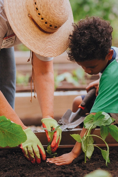 Master gardener, Sue Simon helps one of the youngest volunteers with planting tips.