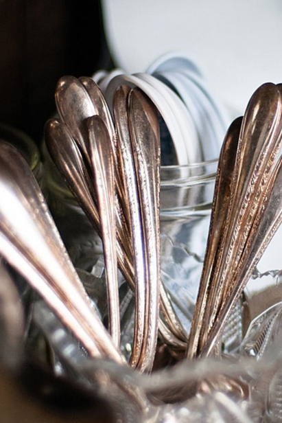 Silverware is displayed in glasses on the countertop.